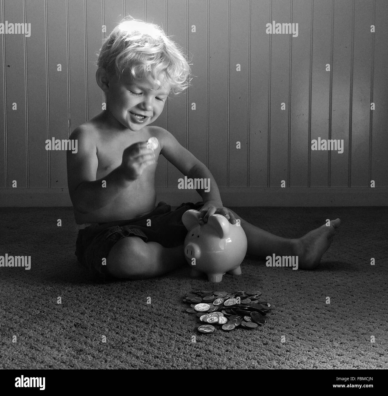 Boy playing with money and piggy bank - Stock Image