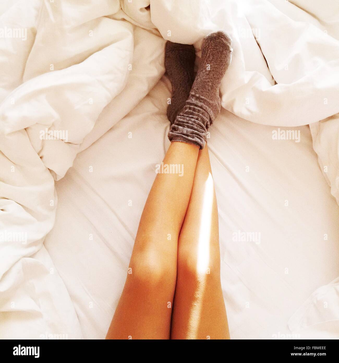 Woman's legs on white sheets - Stock Image