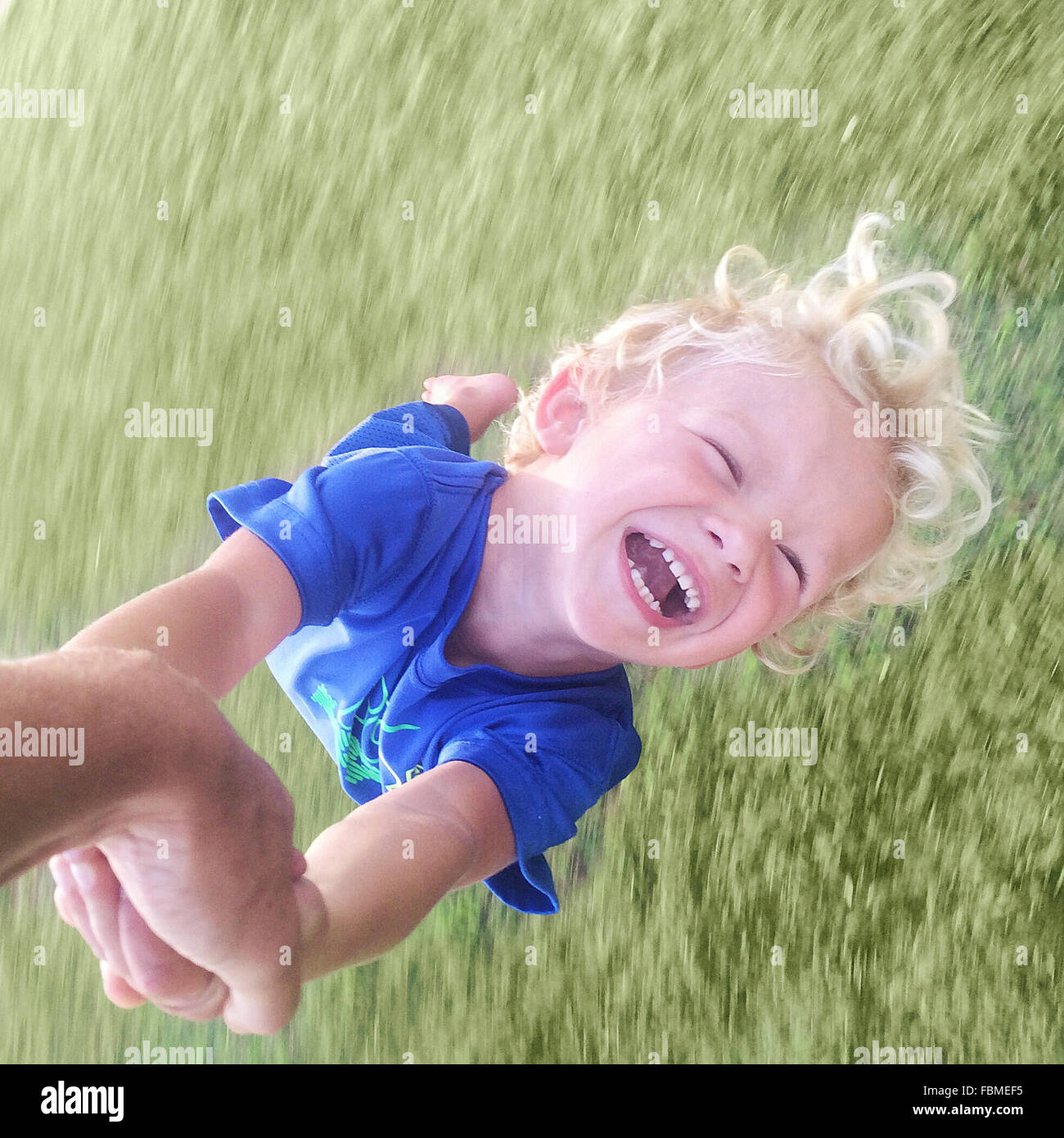 Father spinning boy around - Stock Image