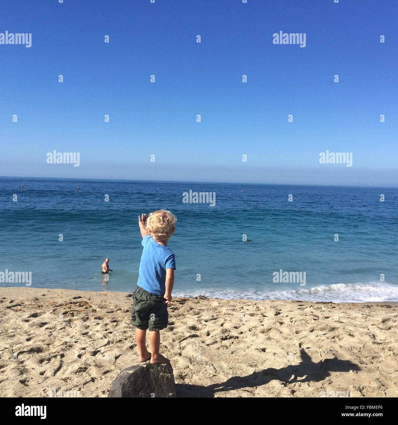 Rear view of boy standing on rock at beach waving at father - Stock Image