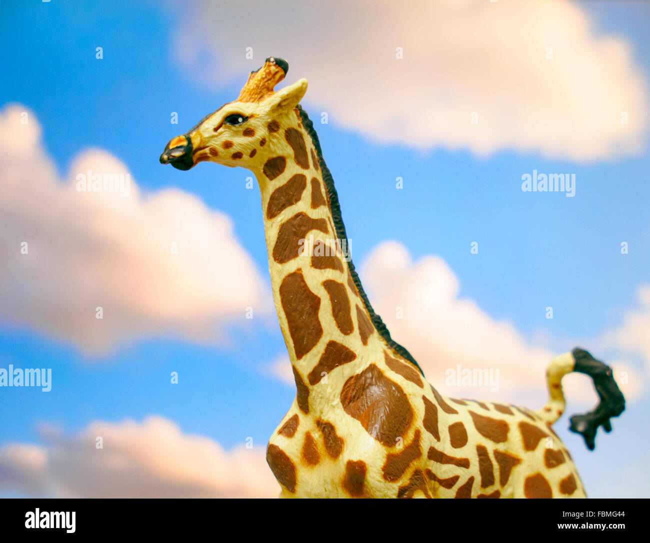 Toy giraffe on cloudy sky background - Stock Image