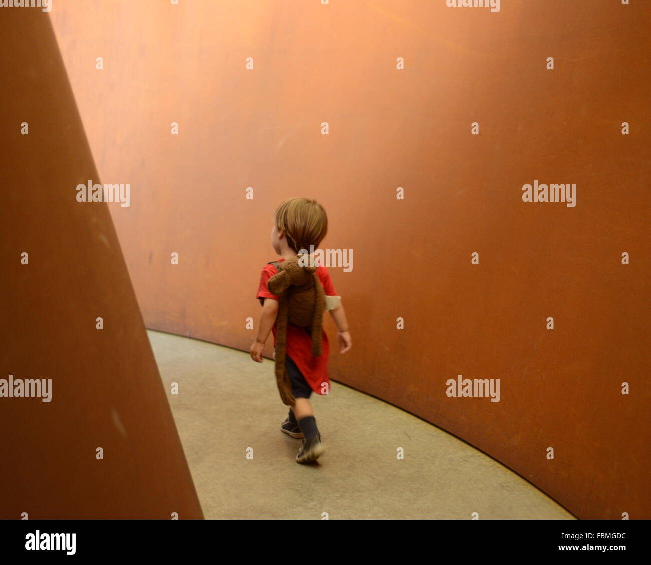Full Length Rear View Of Boy Walking In Passageway - Stock Image
