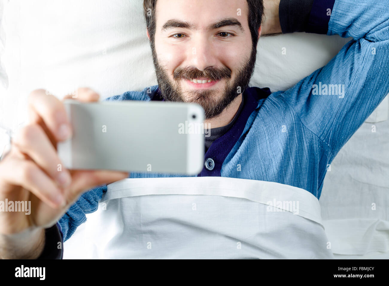 Smiling Man with Pajamas Taking a Selfie with a Smartphone - Stock Image