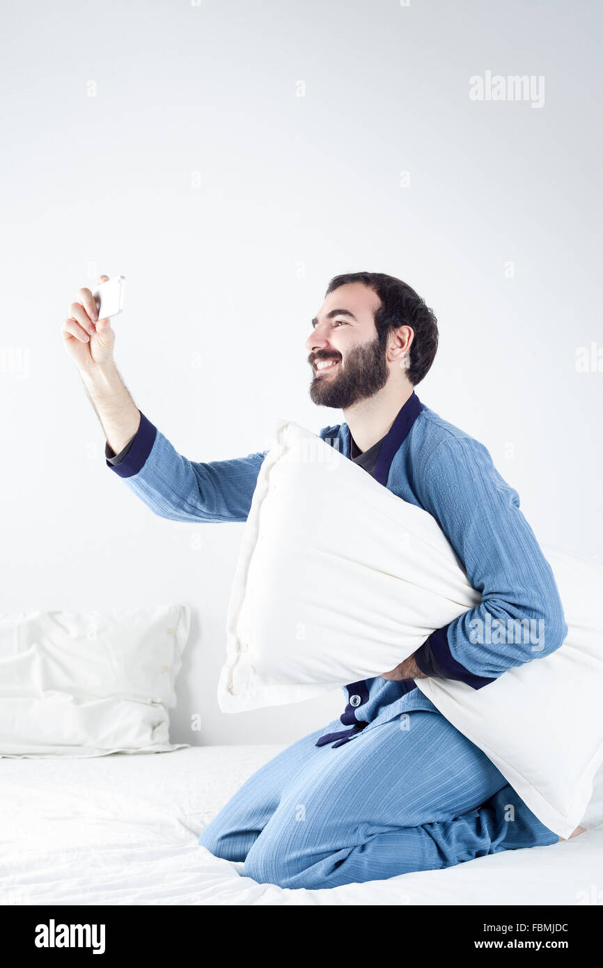 Man with Pajamas on Bed Taking a Selfie with a Smartphone - Stock Image