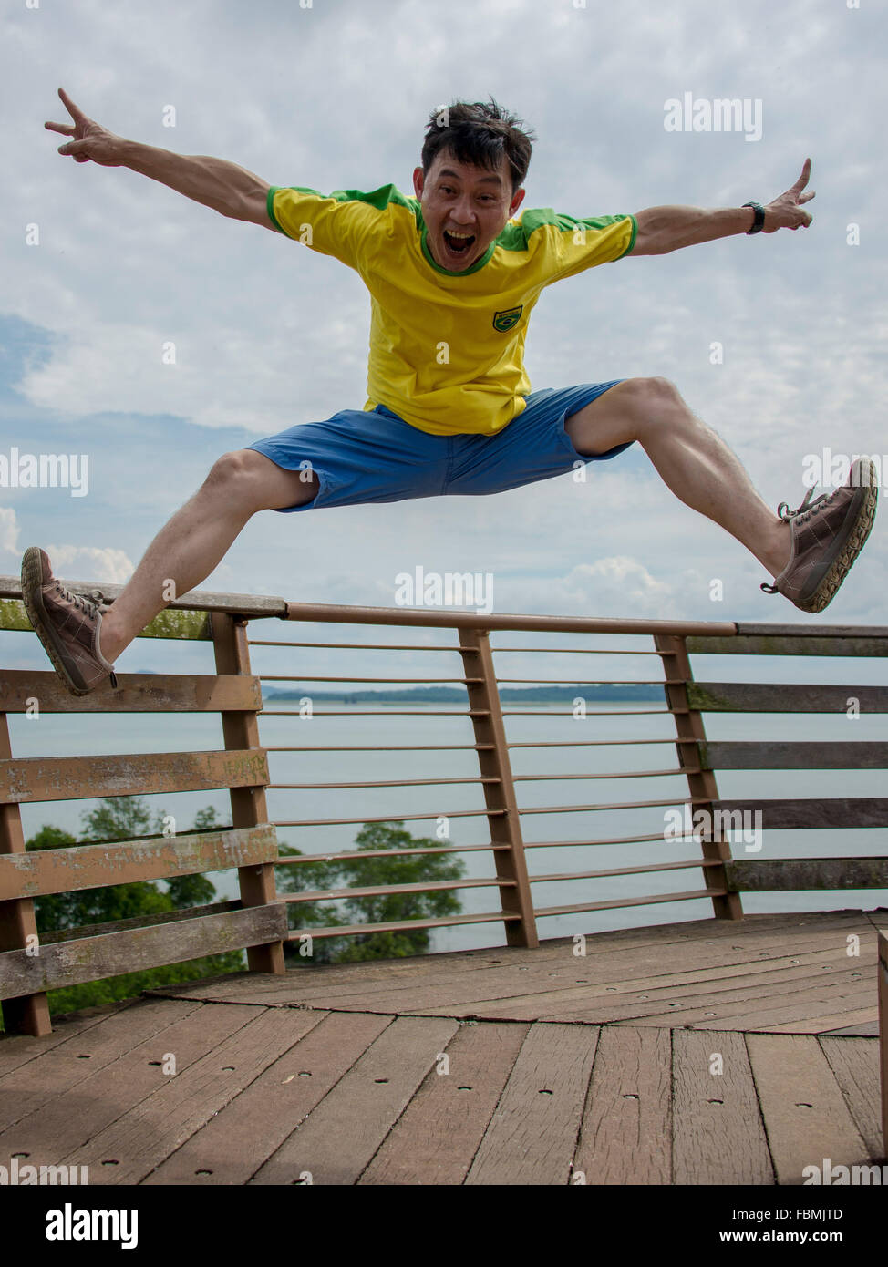 Happy Man Shouting While Jumping On Boardwalk - Stock Image