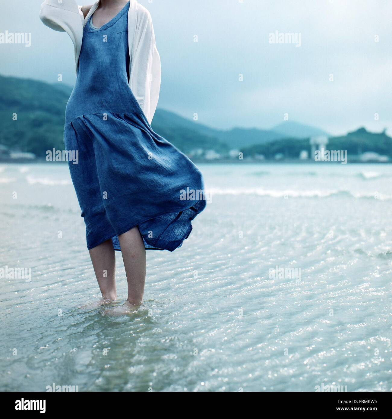 Low Section Of Woman Standing In Water By Shore Stock Photo