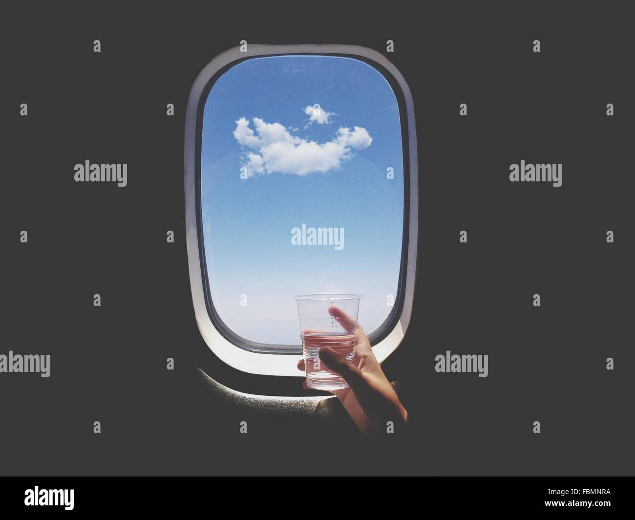Close-Up Of Hand Holding Glass Of Water In Front Of Airplane Window - Stock Image