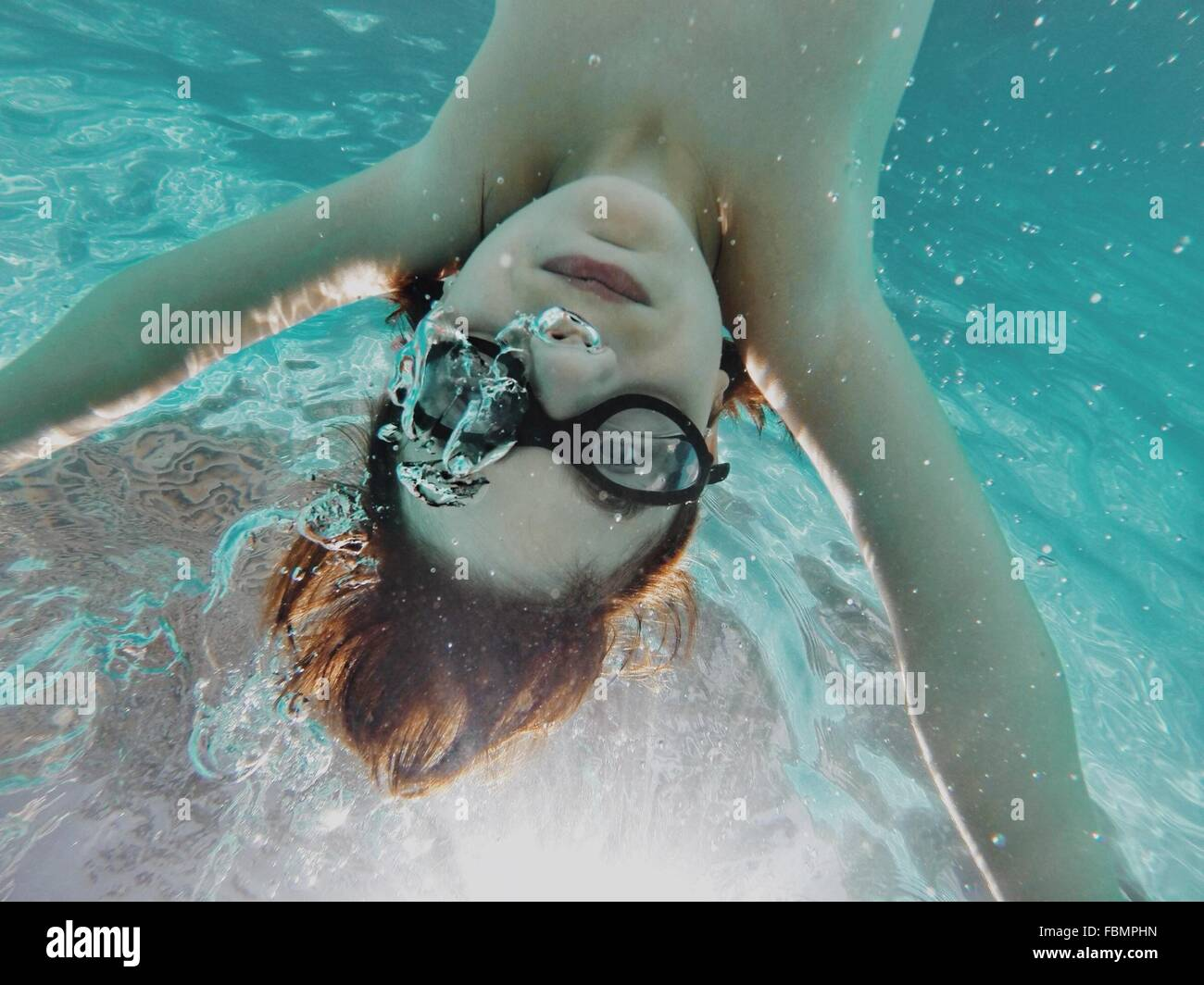 Upside Down Image Of Boy Swimming In Swimming Pool - Stock Image