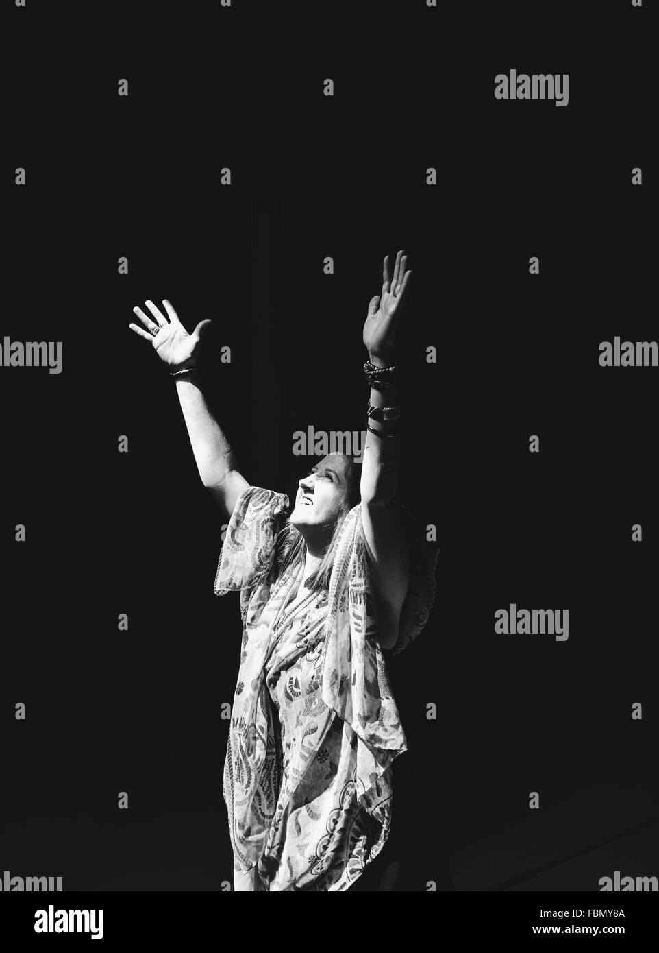 Young Woman Raising Hands Over Black Background Stock Photo