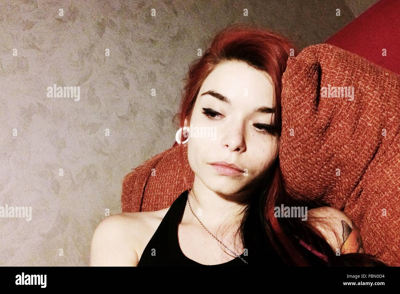 Thoughtful Young Woman Resting On Sofa - Stock Image