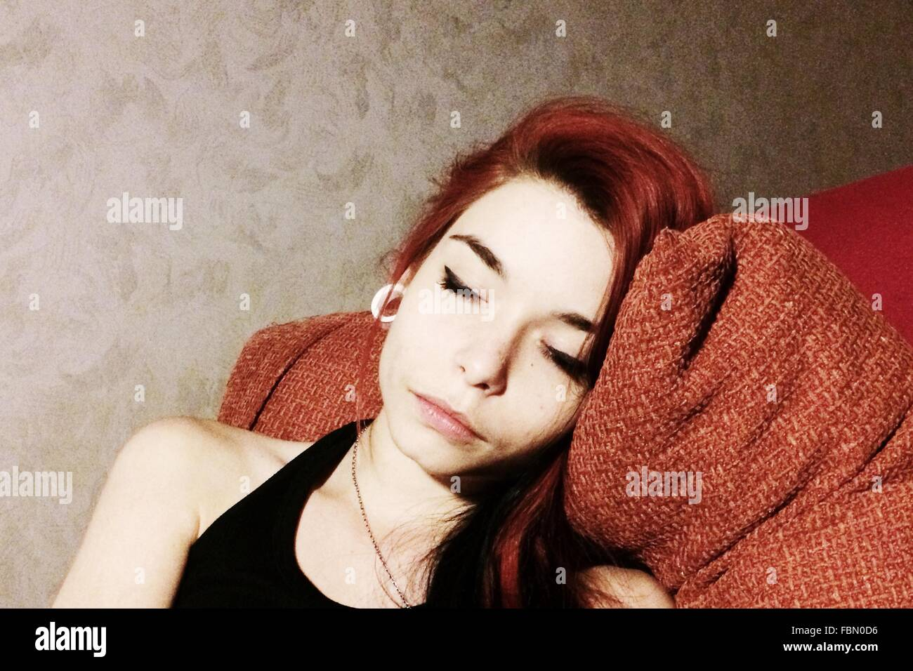 Young Woman Resting On Sofa Against Wall - Stock Image
