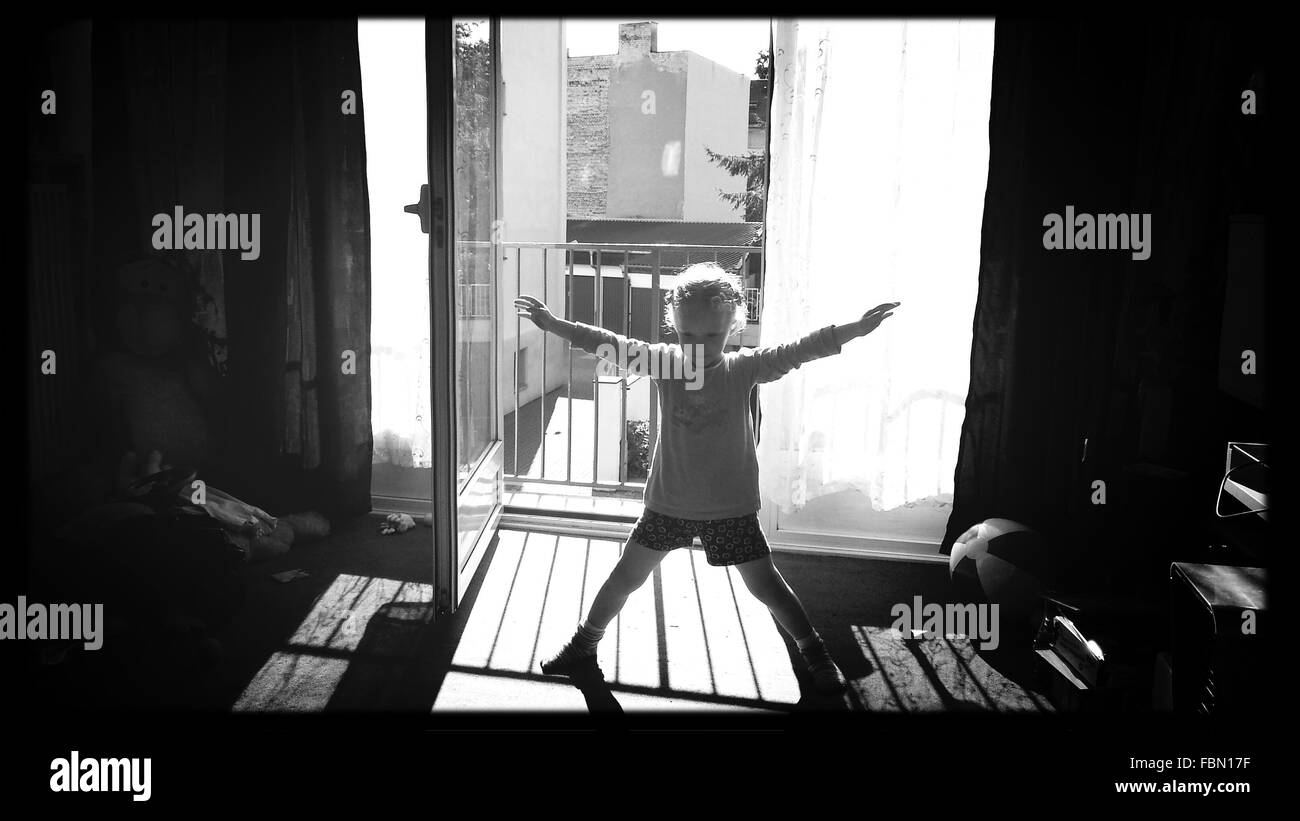 Full Length Of Girl With Arms Outstretched And Legs Apart At Home - Stock Image