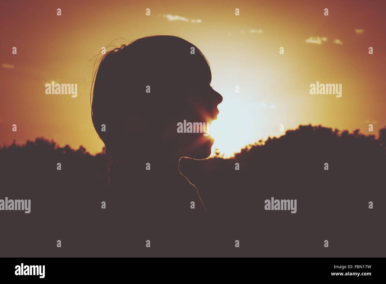 Optical Illusion Of Silhouette Boy Eating Sun At Sunset - Stock Image