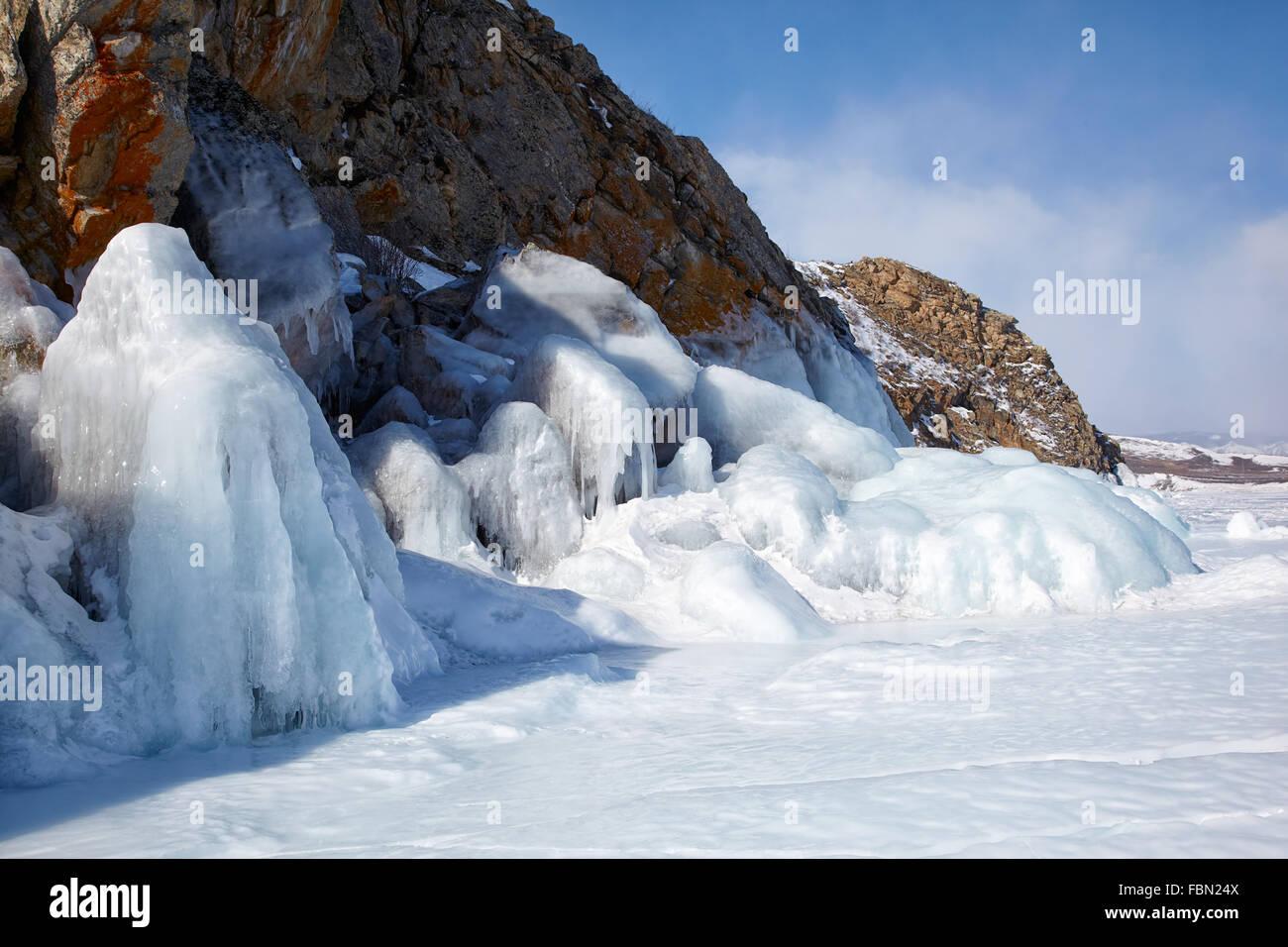 Rocks covered by ice on winter siberian Baikail lake under blue sky backgroun Stock Photo