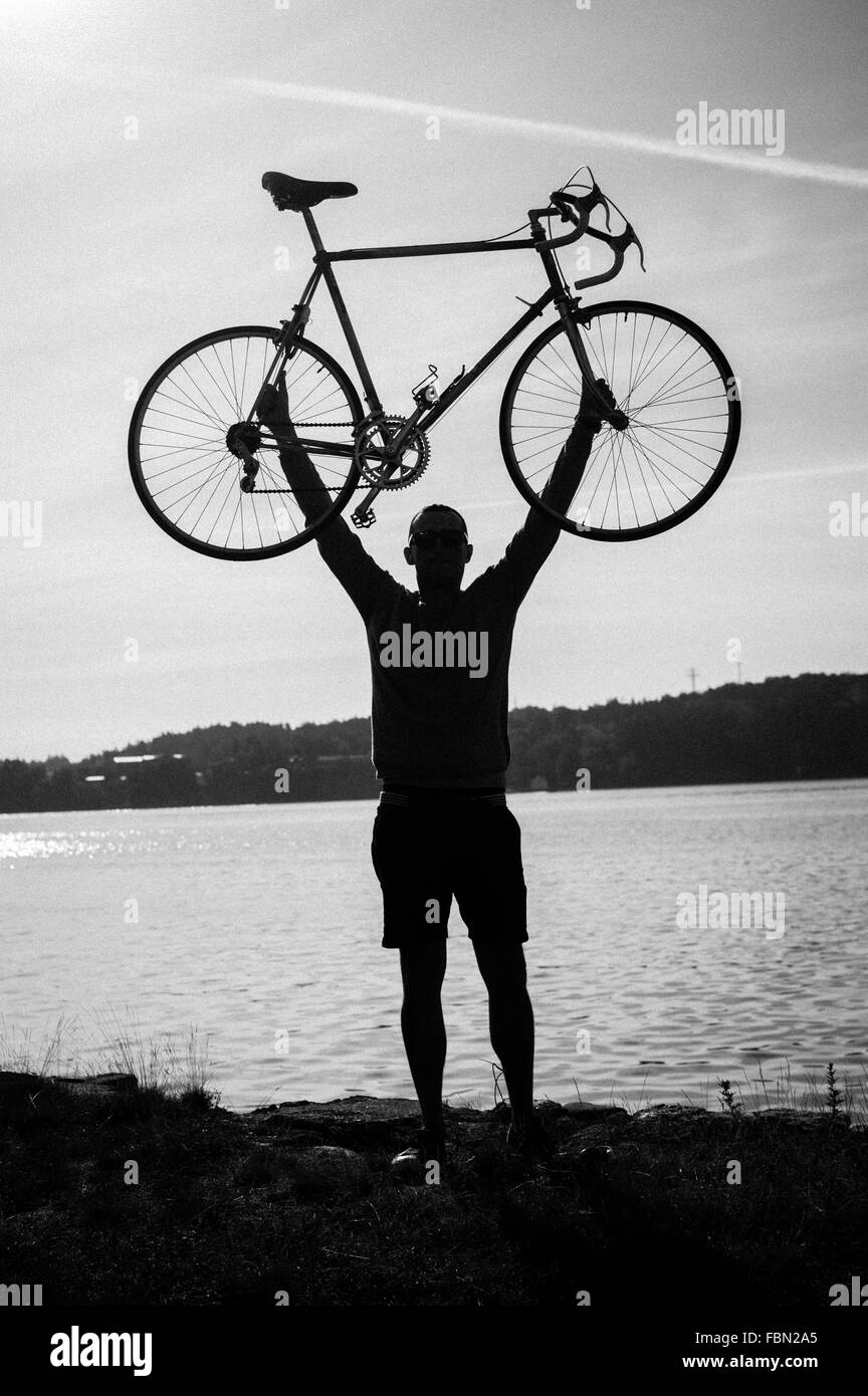 Silhouette Man Lifting Bicycle Against Lake - Stock Image