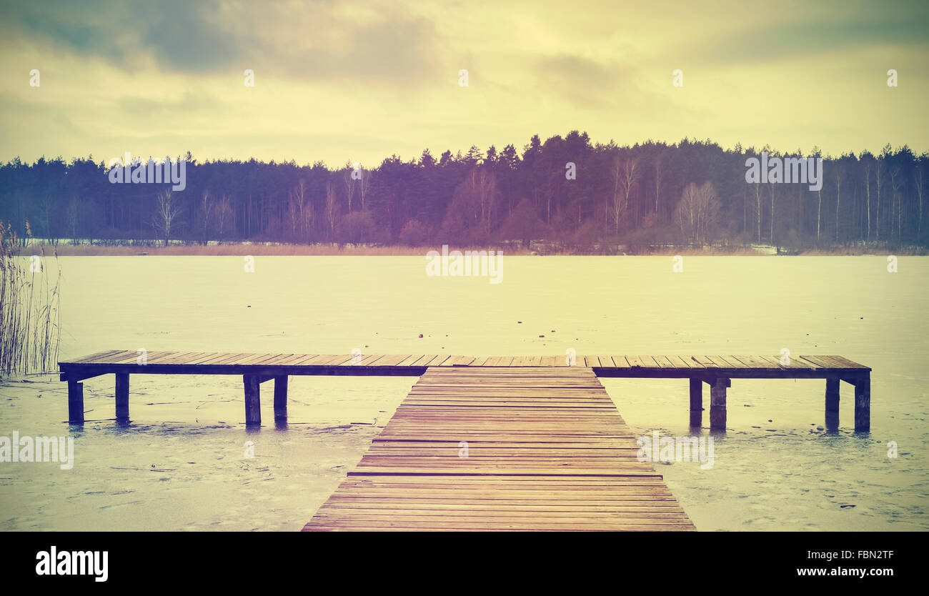 Vintage retro stylized image of a pier on frozen lake. Stock Photo