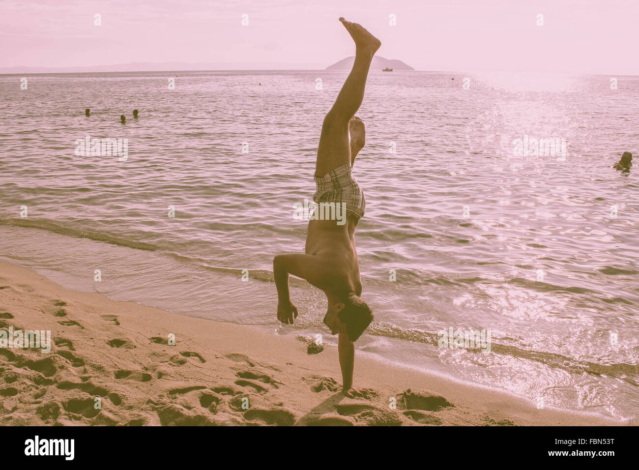 Man Doing Handstand On The Beach - Stock Image
