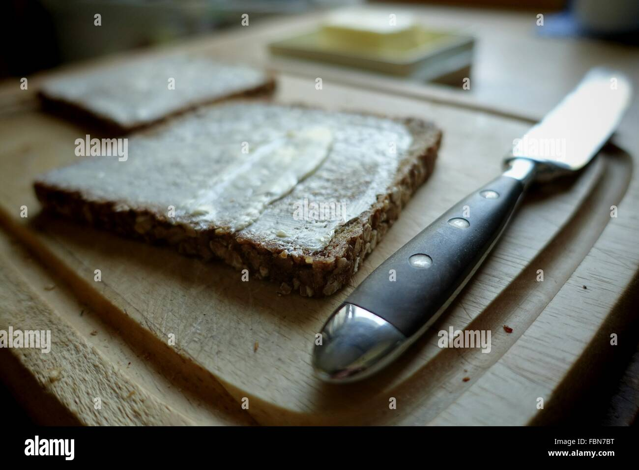 Knife By Bread With Butter On Cutting Board - Stock Image
