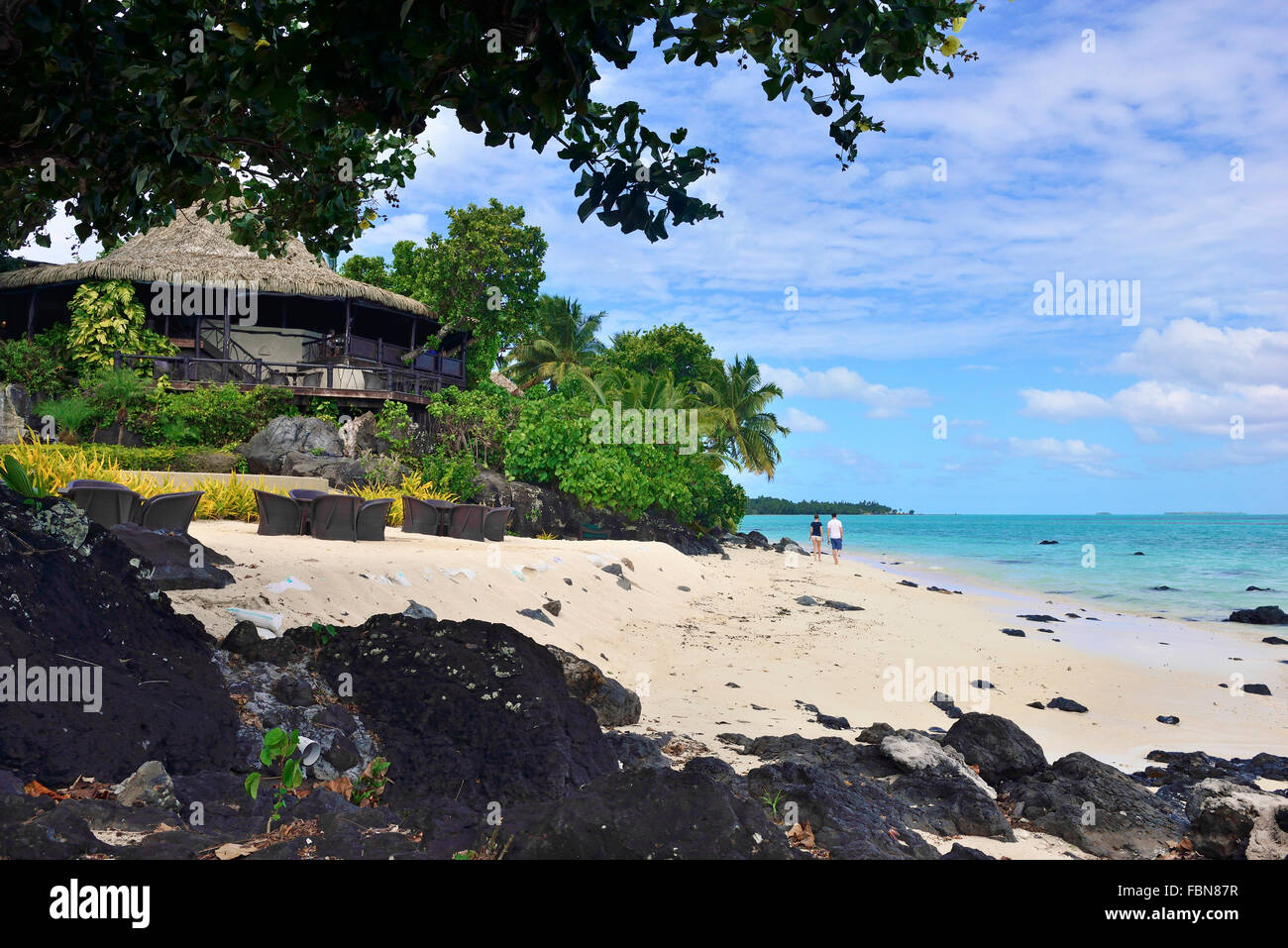 Guests relaxing, strolling  along  the sandy  beach  foreshore at Pacific Resort Aitutaki .Aitutaki Cook Islands - Stock Image