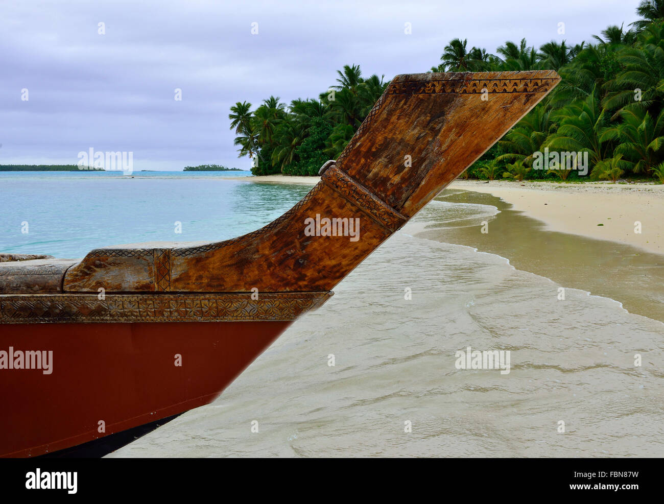 Prow of a traditional polynesian wooden boat or Vaka on the beach and lagoon of tropical One Foot Island, Aitutaki, Stock Photo