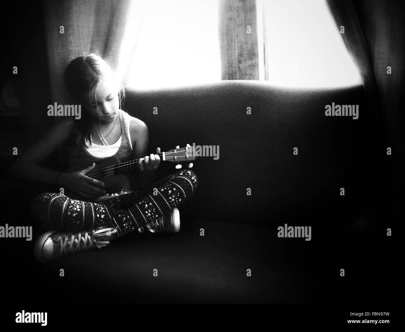 Girl Playing Ukulele In House - Stock Image