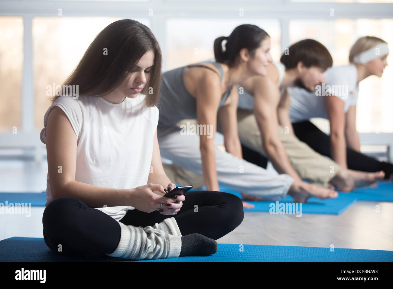 Tired or lazy woman sitting cross-legged, resting during practice in sports club, using phone, reading, sending - Stock Image
