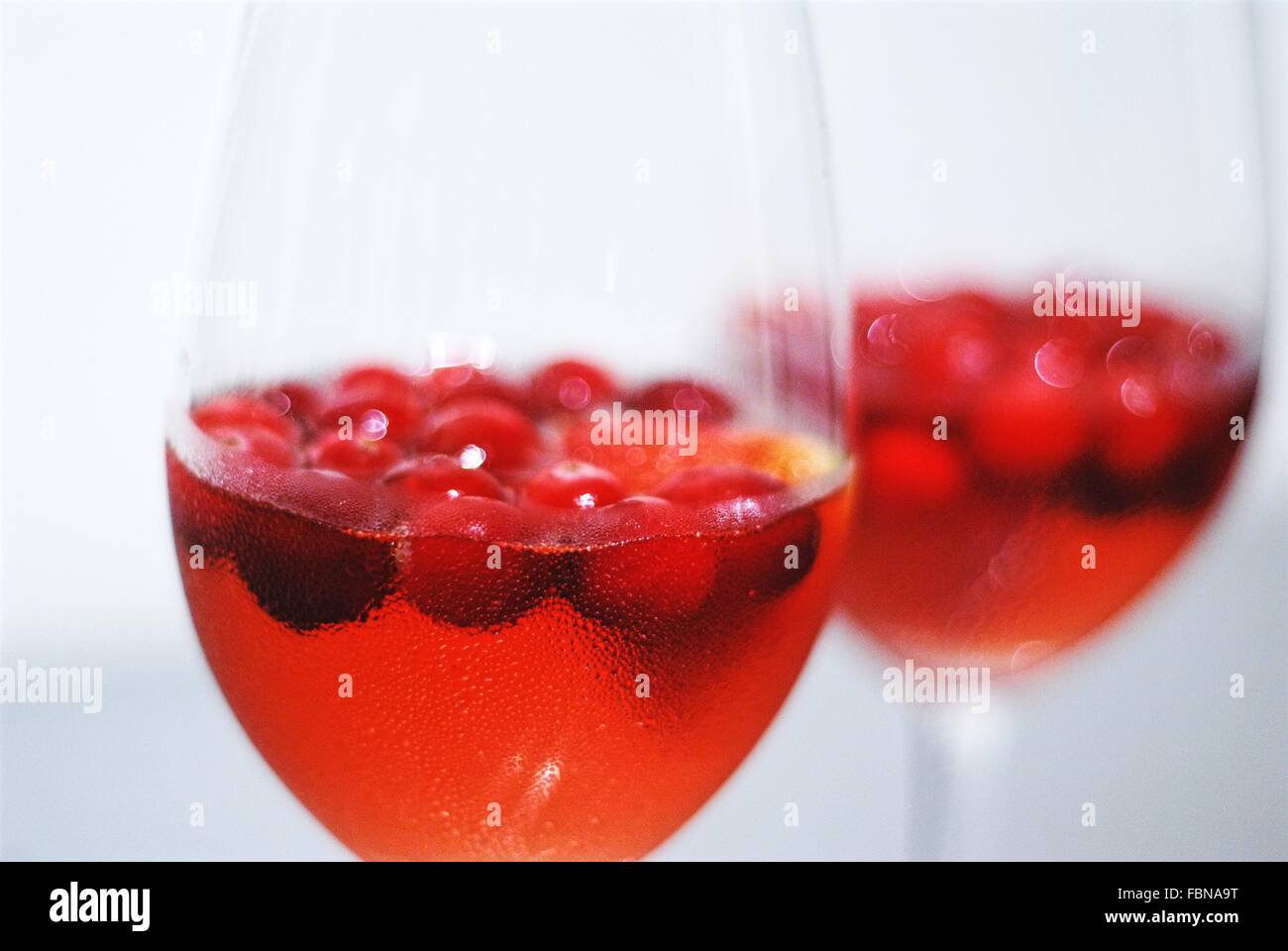 Two glasses with chilled cocktail and fresh cranberries or cranberry juice and fresh cranberries. One glass is in - Stock Image