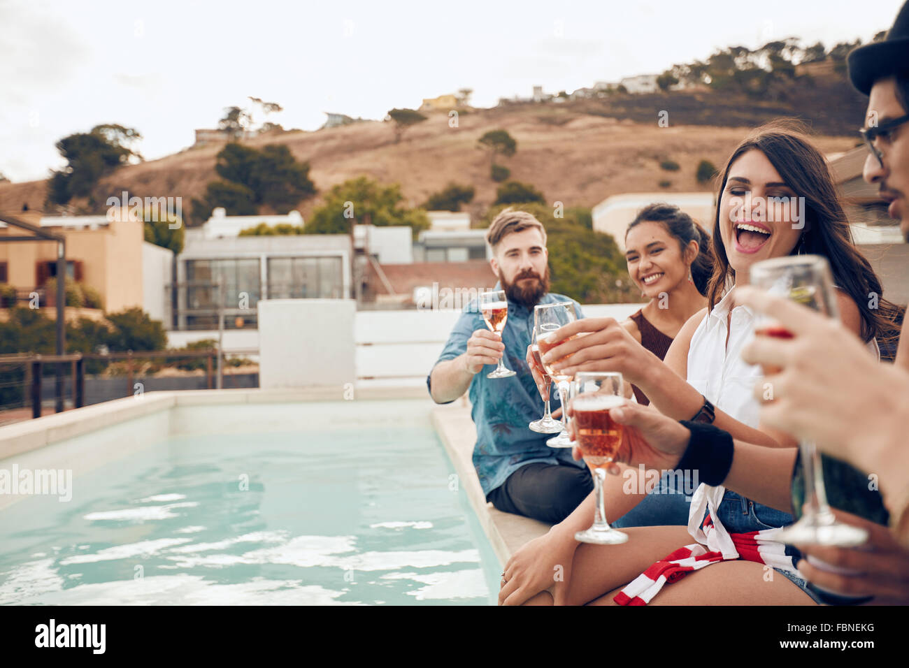 Outdoor shot of happy group of young people sitting on the edge of the pool drinking wine. Multiracial friends enjoying - Stock Image