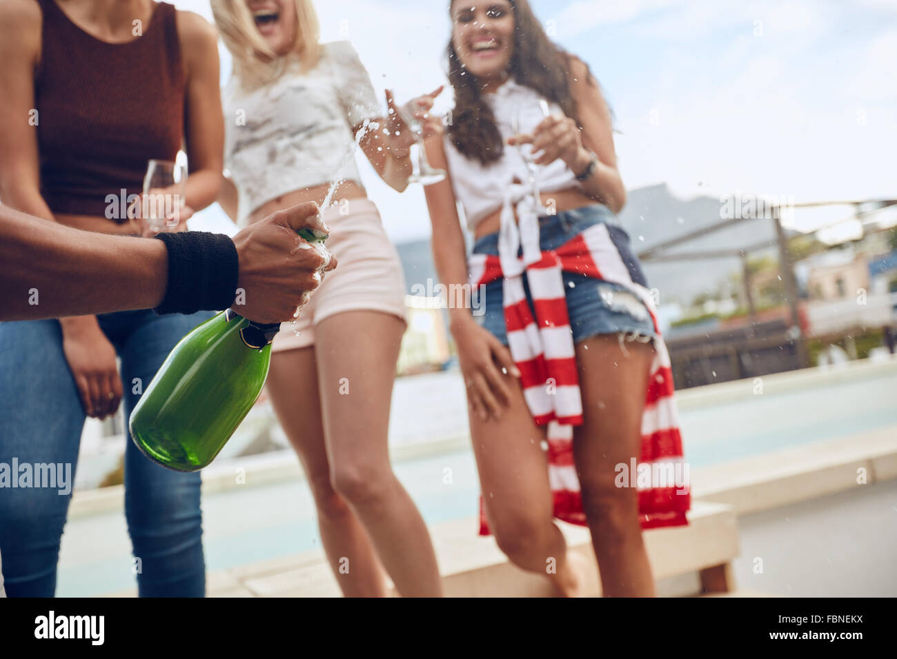 Cropped shot of hand of man holding a champagne bottle with female friends standing in background. Champagne slipping - Stock Image