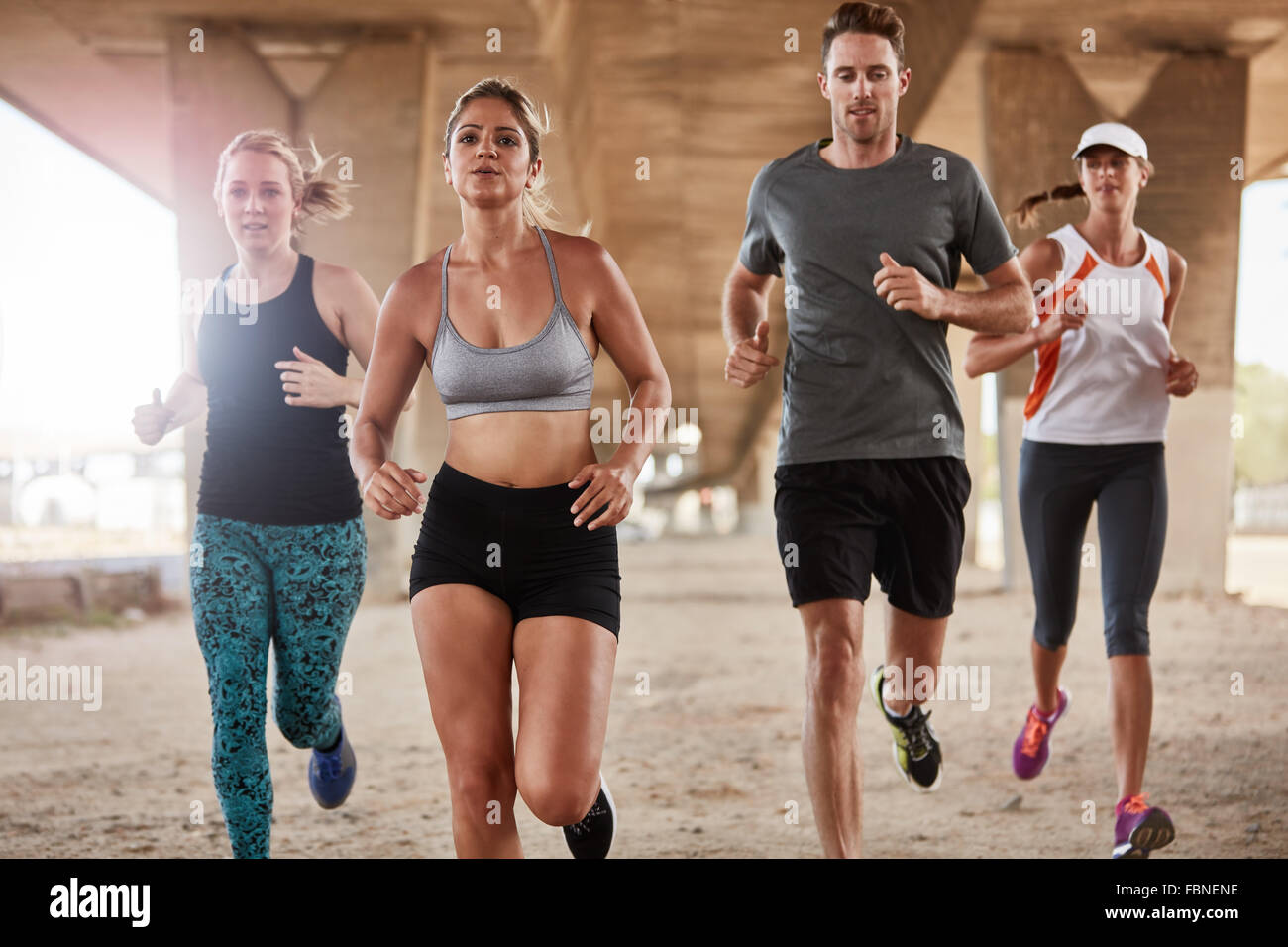 Healthy young people running together in morning under a bridge.. Runners training together. - Stock Image