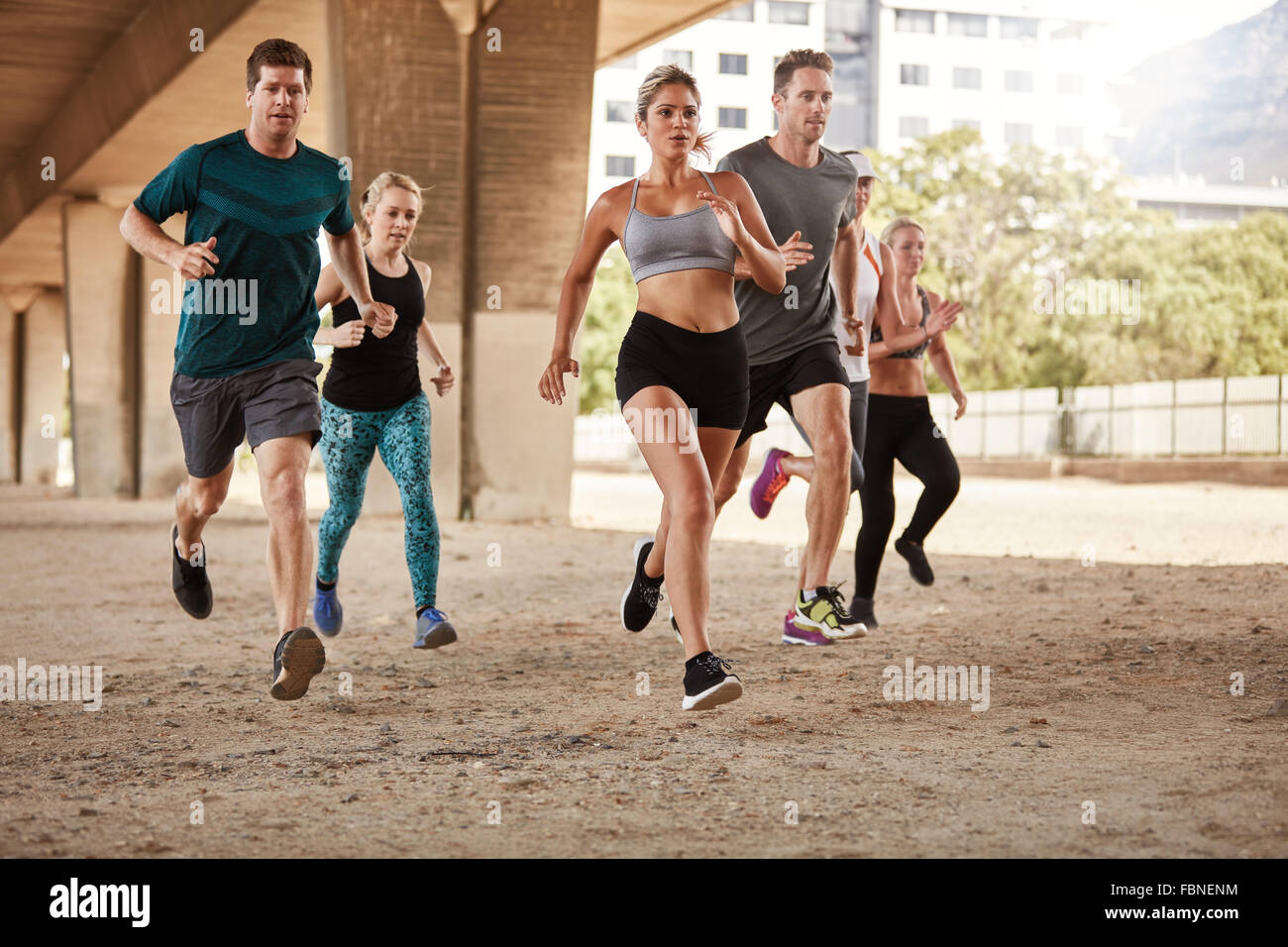 Determined  group of young people running together in city. Running club members training together. - Stock Image