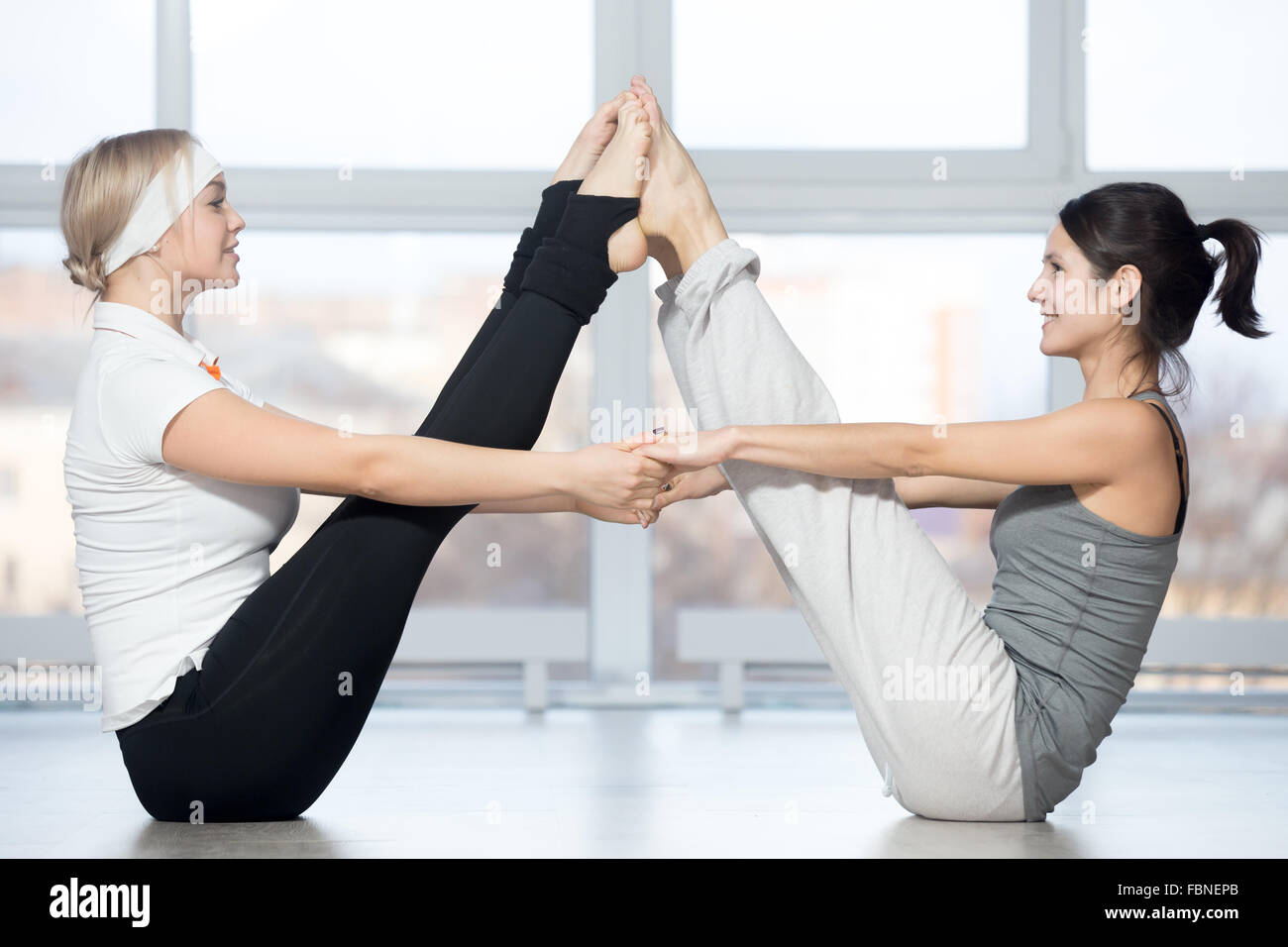 Group of two beautiful fit young people working out in sports club, doing asana for abs in pair Ubhaya Padangusthasana - Stock Image