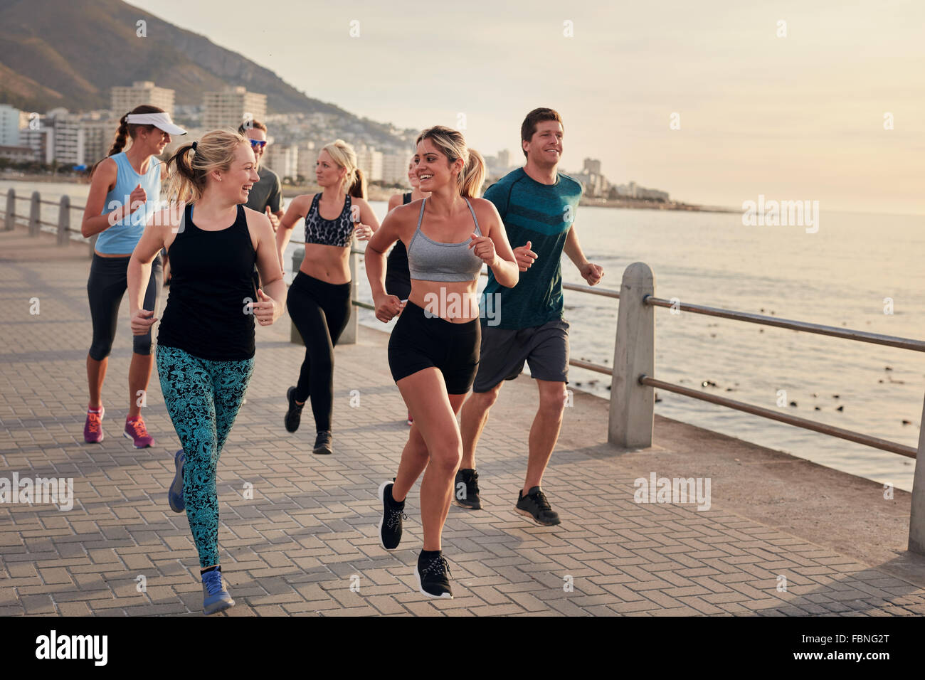 Portrait of young runners enjoying workout on the sea front path along the shoreline.  Running club group running - Stock Image