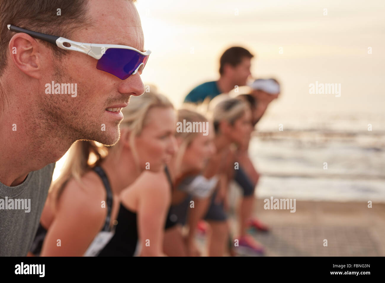 Closeup shot of focused and determined young man standing at starting line with competitors in background. Runners - Stock Image