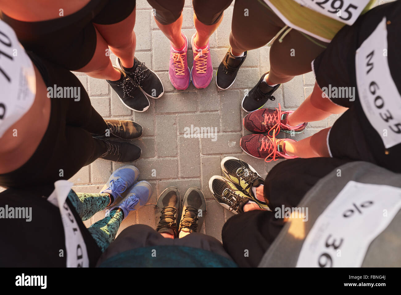 Top view of feet of people standing in a circle. Runners standing in a huddle with their feet together. - Stock Image
