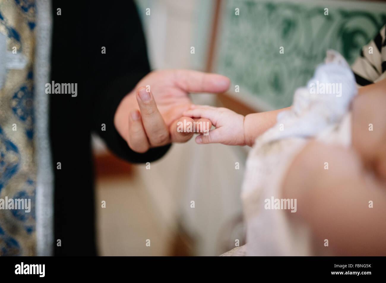 holding baby hand during christening Orthodox baptism - Stock Image