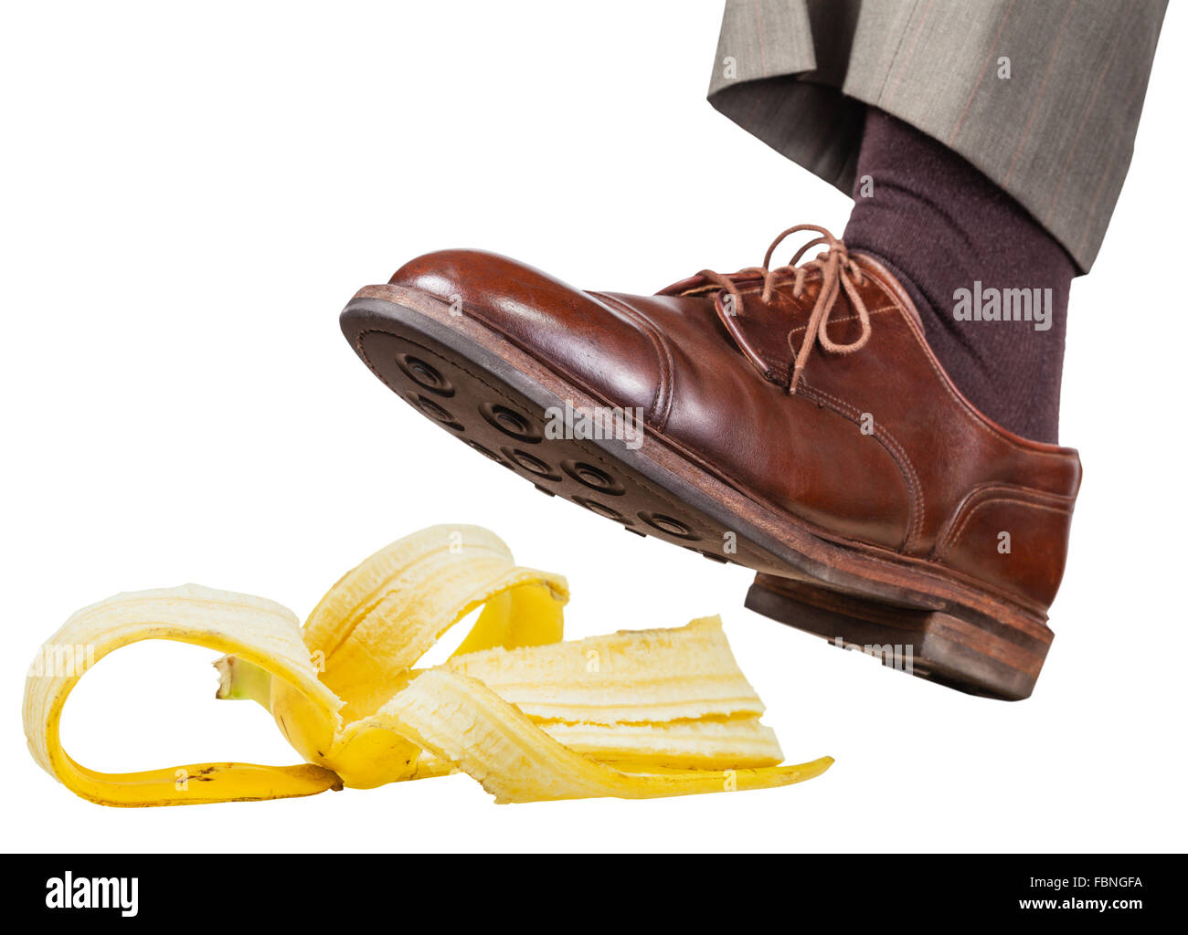 male foot in the left brown shoe slips on a banana peel isolated on white background Stock Photo