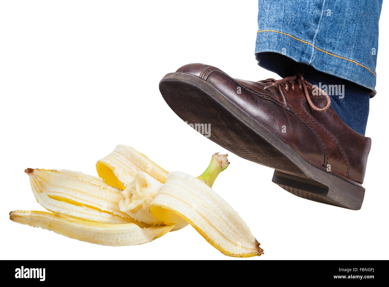 male left foot in jeans and brown shoe slips on a banana peel isolated on white background Stock Photo
