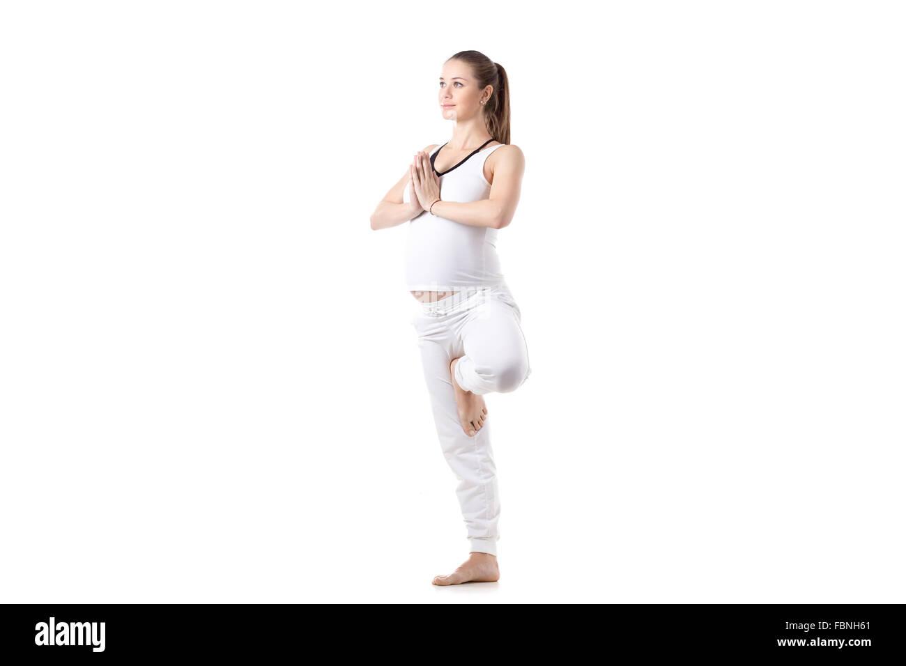 Full length portrait of young pregnant fitness model in white sportswear doing yoga or pilates training, Vrikshasana, - Stock Image