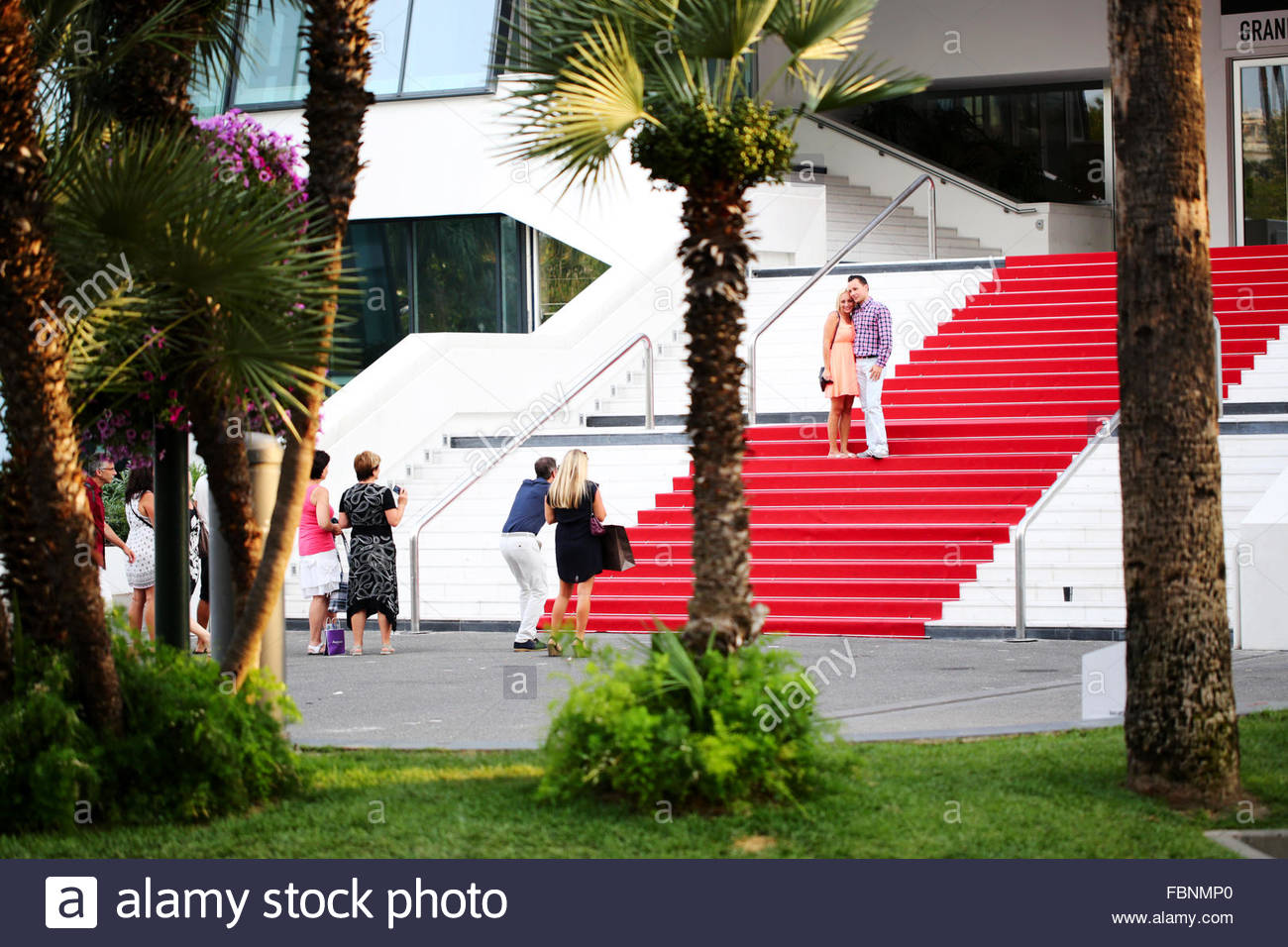 A couple of tourists pose on the red carpet outside of the Palais des Festivals in Cannes, France  whist their friends - Stock Image