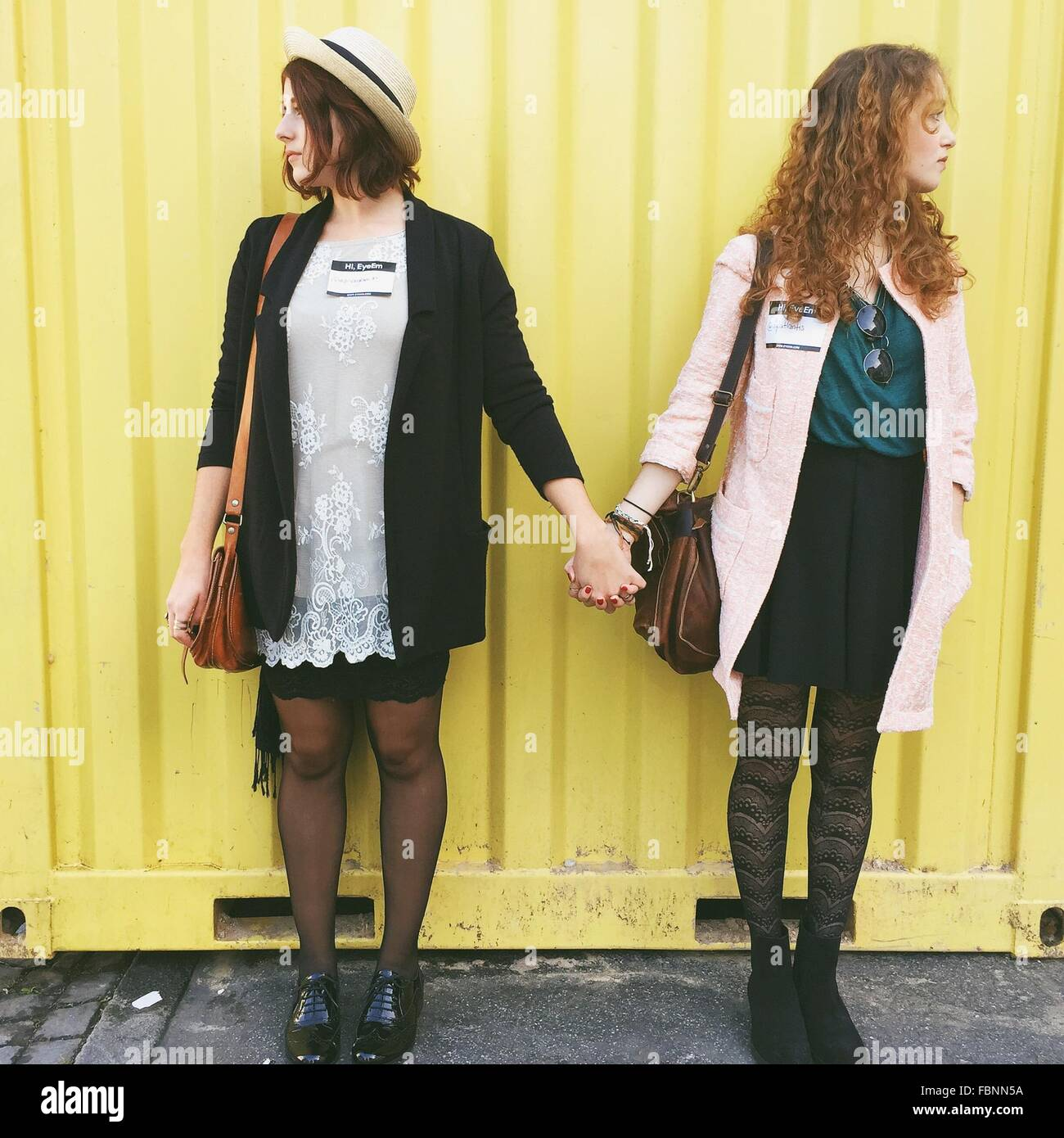 Young Female Friends Holding Hands While Looking Away Against Cargo Container - Stock Image