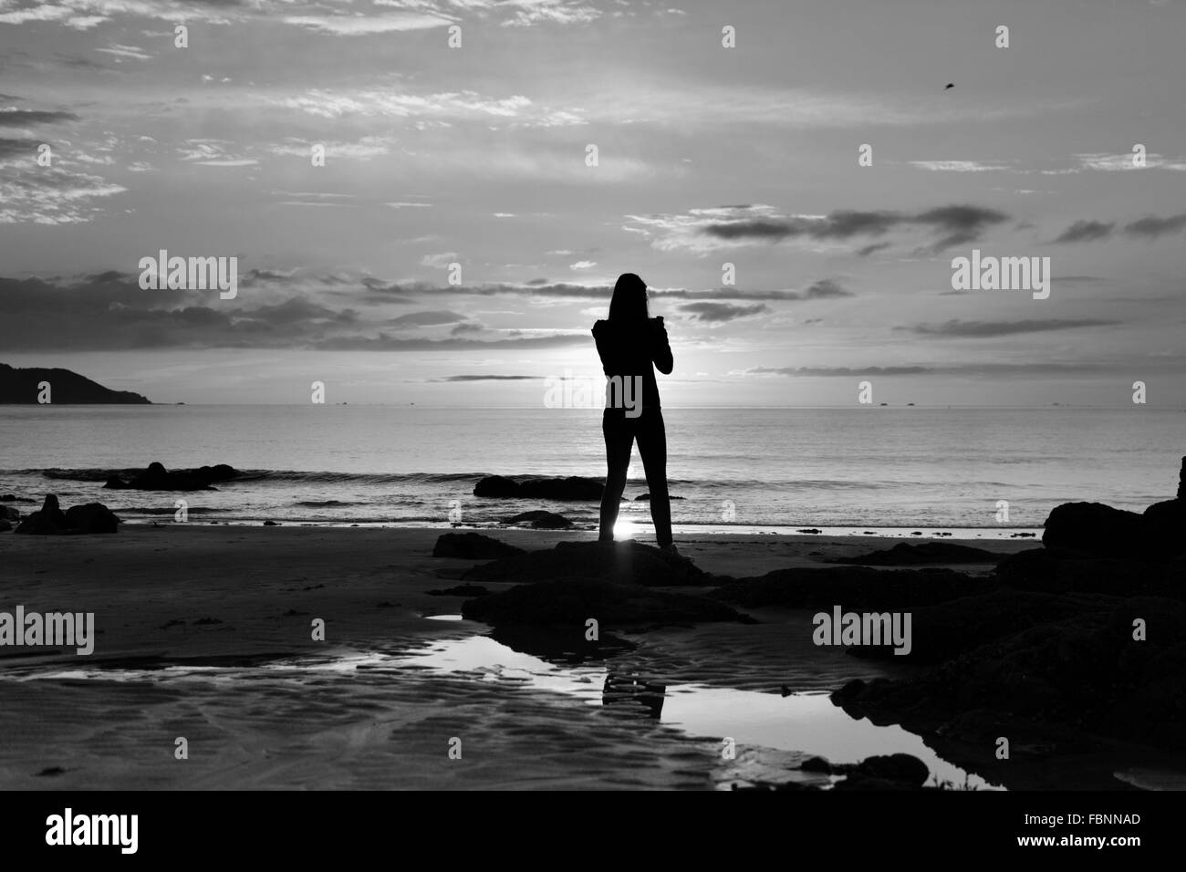 Silhouette Of Woman On Beach At Sunrise - Stock Image