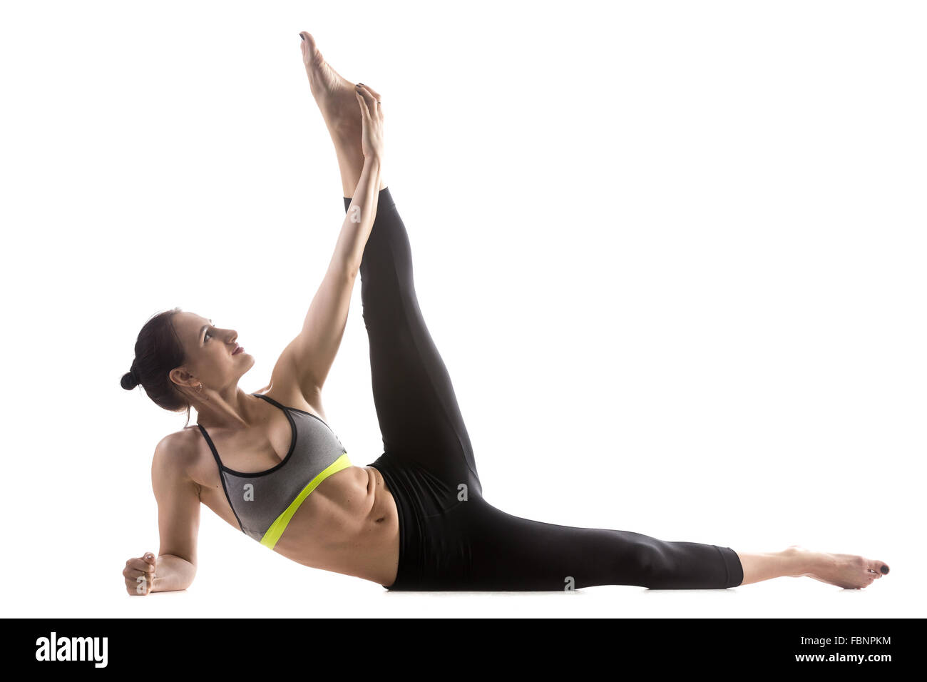 Sporty fit beautiful young woman in sportswear bra and black pants working out, doing Anantasana, Side-Reclining - Stock Image