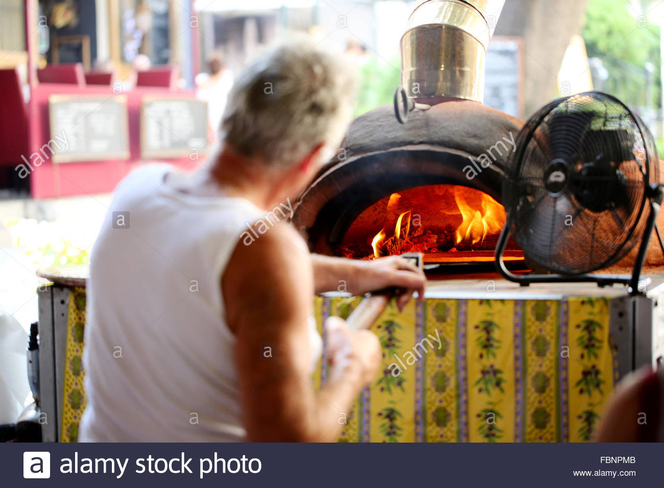 An older man, wearing a vest, pushes a spatula into an open, flaming, cast iron pizza oven in a covered market area - Stock Image