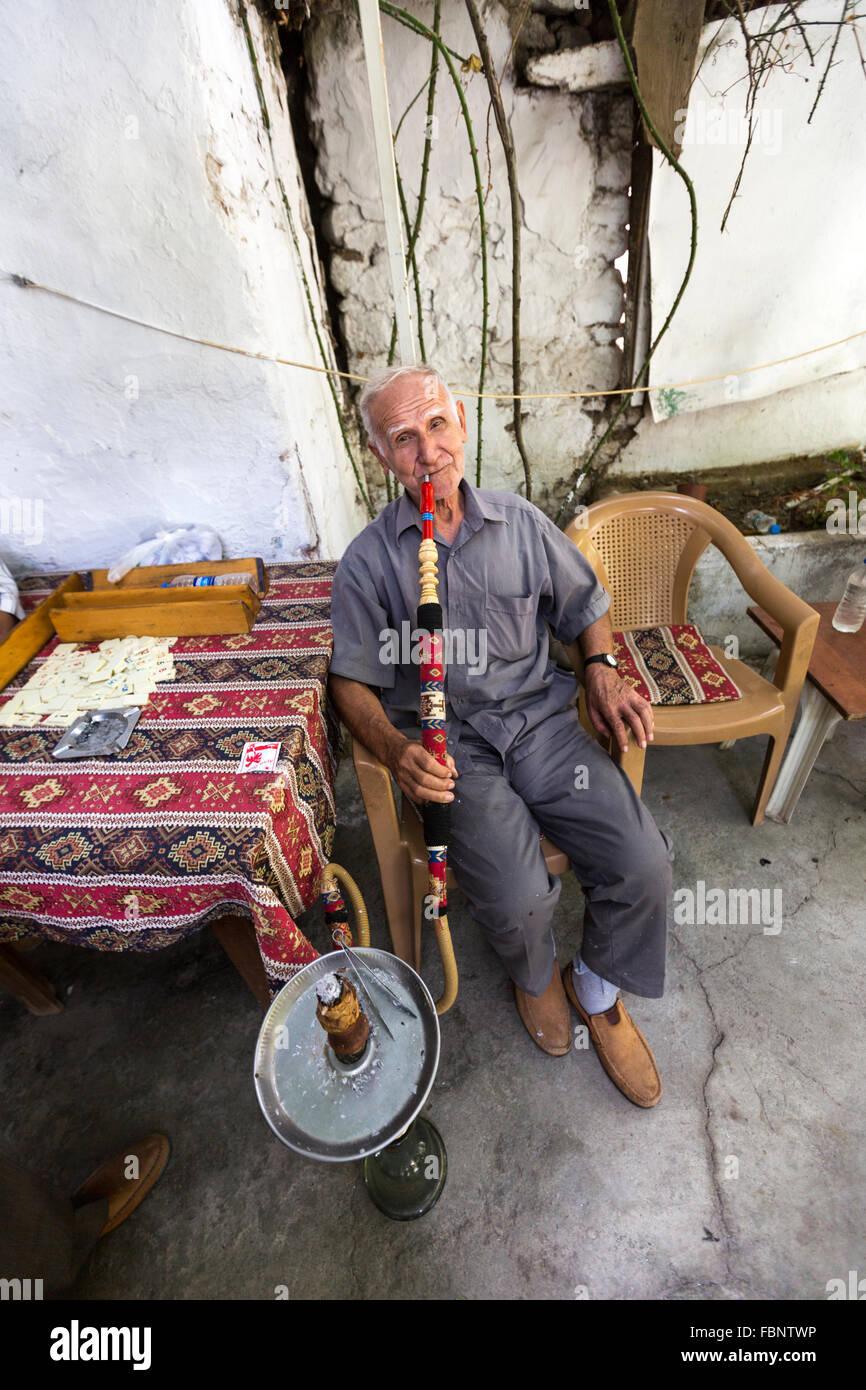 Old man sitting outside a cafe smoking a water turkey shisha smoke pipe in the Old Pergamon bazaar, Bergama. - Stock Image