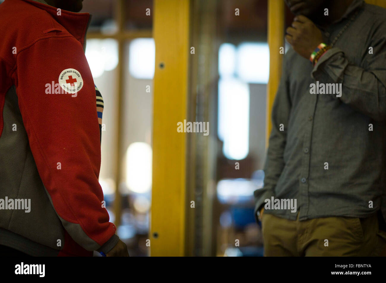 a British Red Cross volunteer chats with man at a drop in centre - Stock Image