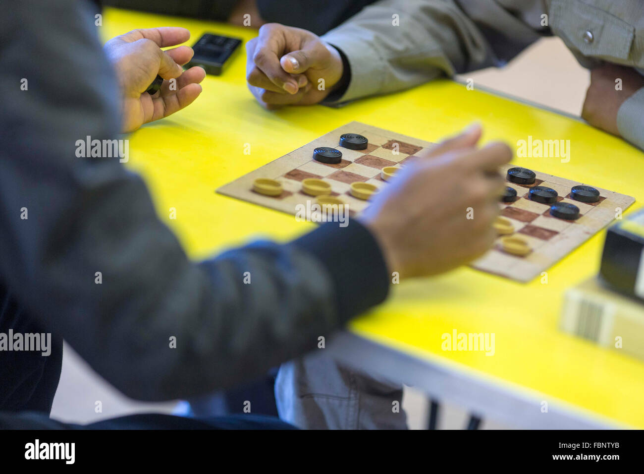 Two unidentifiable men play a game of draughts (US - checkers) at a community centre  Photo credit : Chris Bull - Stock Image