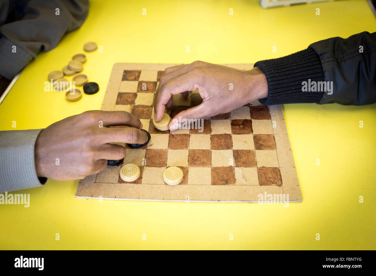 Two unidentifiable men play a game of draughts (US - checkers) at a community centre - Stock Image