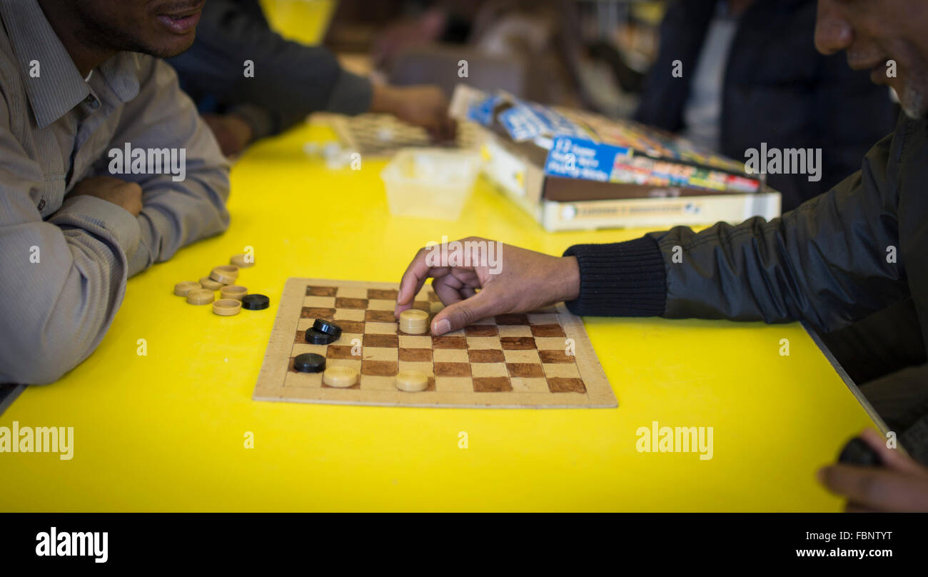 Two unidentifiable men play a game of draughts (US - checkers) at a community centre Stock Photo