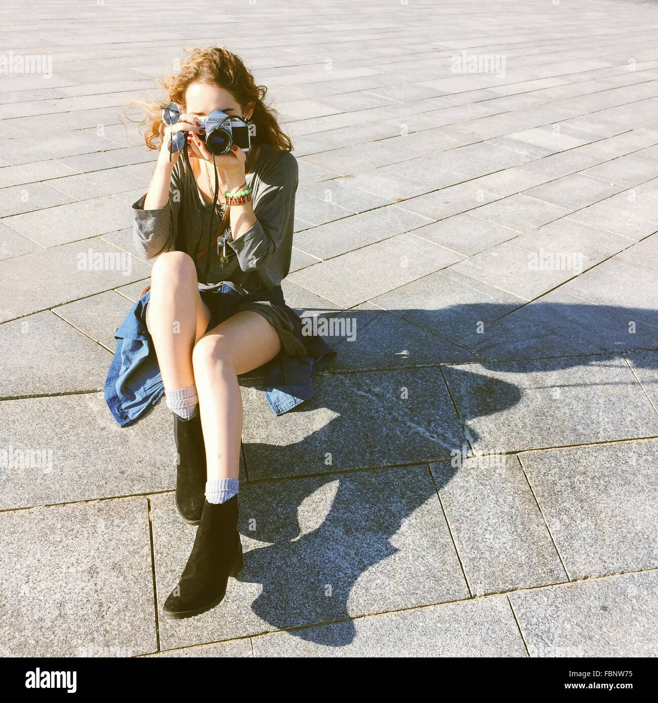 Young Woman Photographing While Sitting On Street - Stock Image